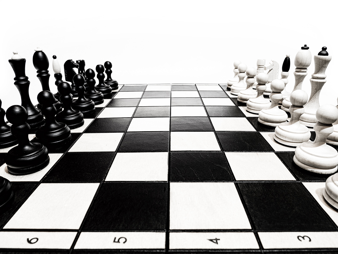Základní postavení černých a bílých figurek na šachovnici stojí proti sobě