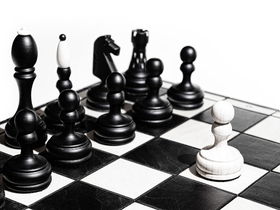 Odvaha, osamocený bílý pěšec stojí na šachovnici před černými figurkami