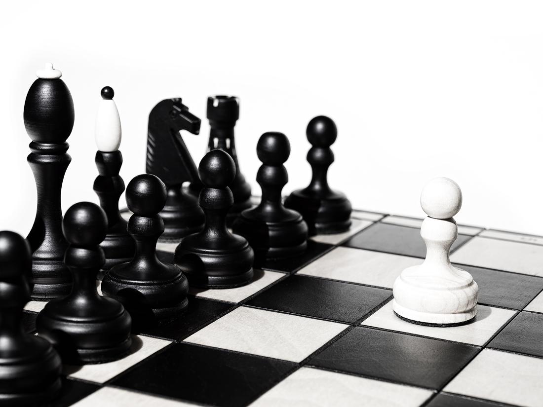 Osamocený bílý pěšec stojí na šachovnici před černými figurkami pohled ze shora z boku