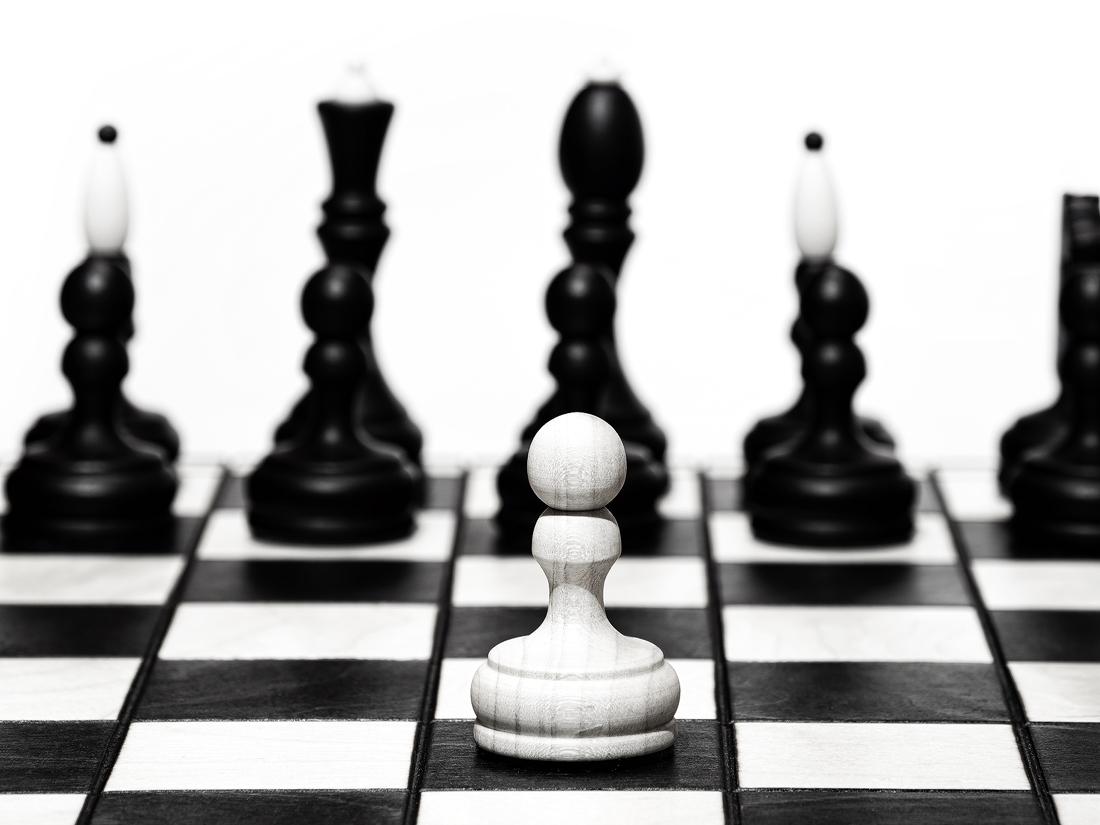 Osamocený bílý pěšec stojí na šachovnici před černými figurkami, pohled čelně