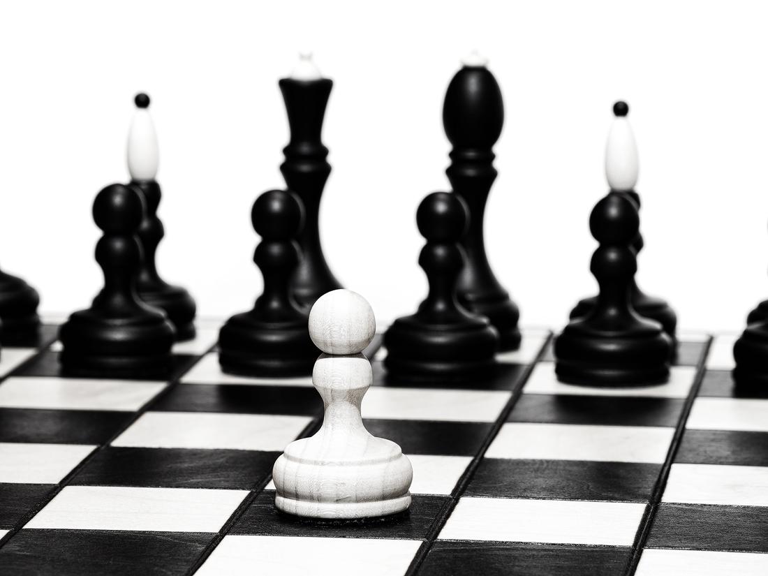 Osamocený bílý pěšec stojí na šachovnici před černými figurkami, pohled téměř čelně