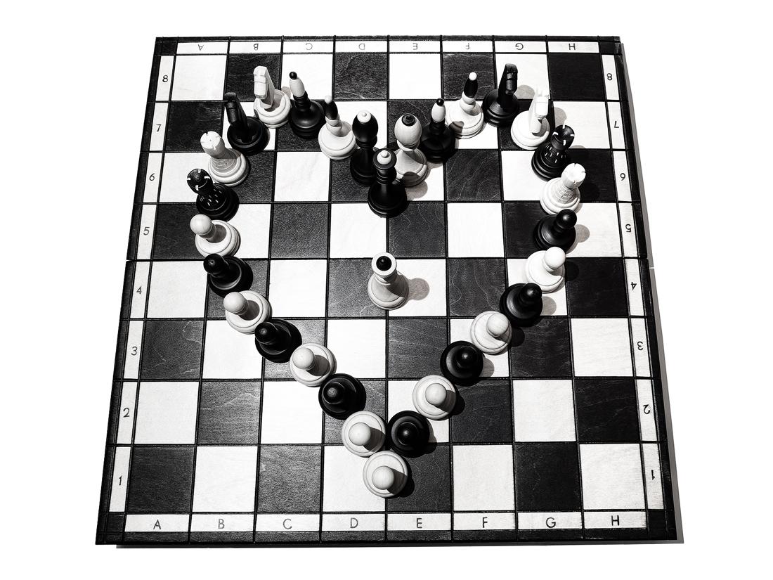 Srdce z šachových figurek na šachovnici pohled shora
