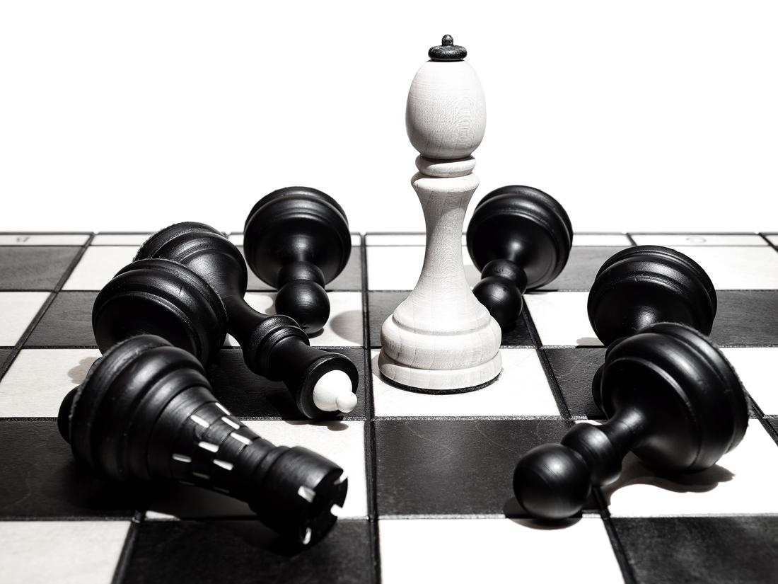 Bílý král stojí vítězně na šachovnici a ostatní černé figurky jsou poražené, leží